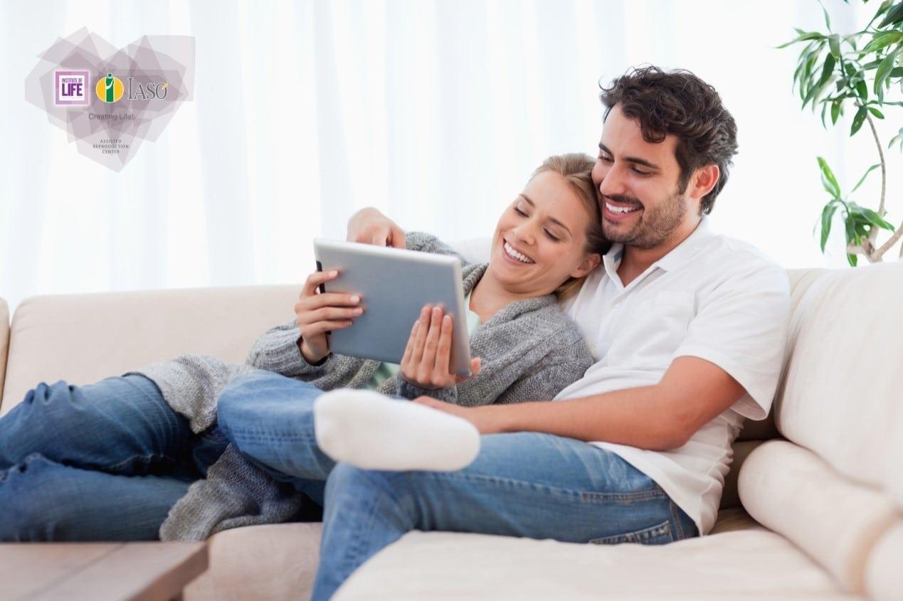 iolife - ζευγάρι στον καναπέ κοιτάζει σε tablet