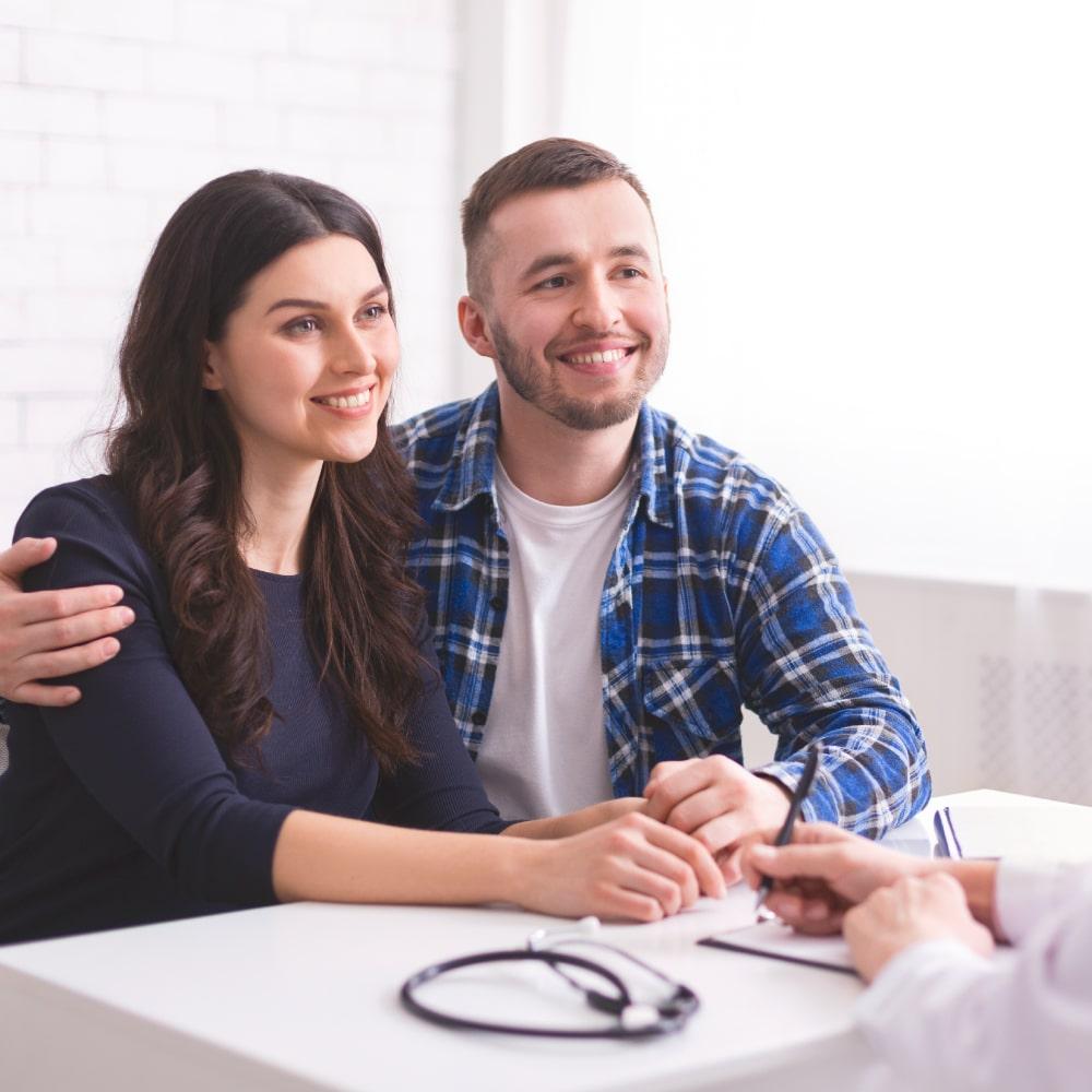 χαρούμενο ζευγάρι αγκαλιά συμβουλεύεται γιατρό Institute of Life γιατρός κρατάει σημειώσεις
